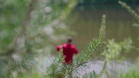 Fischer mit einer Angelrute ist auf der Flussbank Schöne Sommerlandschaft Im Freienerholung liebhaberei stock footage