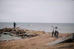Fischer mit Fahrrad auf dem Ufer des Finnischen Meerbusens im wolkigen Wetter stockfotos