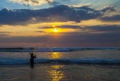 Fischer mit Netz am Sonnenuntergang Stockbild