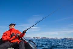 Fischer mit spinnendem Athleten in seinen Händen Fischerei von einer Boa Stockfoto