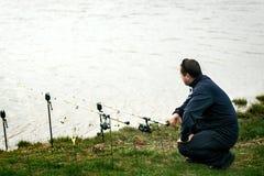 Fischer nahe seinen Stangen, die warten, um zu fangen Lizenzfreie Stockfotos