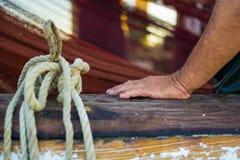 Fischer ` s Hand mit Fischernetz im Hintergrund Nasse und geknitterte Hand, die auf einem hölzernen Boots-Zaun sich lehnt Stockfoto