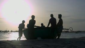 Fischer-Schattenbild-Strecken-rundes Boot, zum an der Hintergrundbeleuchtung auf den Strand zu setzen stock video