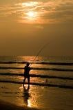 Fischer Silhouettte im Strand-Sonnenaufgang lizenzfreie stockfotos
