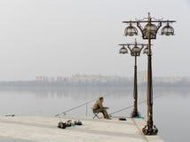 Fischer sitzt auf städtischem Damm und Fischen Stockbild