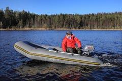 Fischer steuert graues aufblasbares Gummiboot mit einem Außenbord stockbild