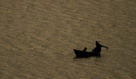 Fischer und sein Hundefischen im Fewa See in Pokhara, Nepal lizenzfreie stockfotografie