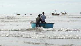 Fischer ziehen das Korbboot am Strand stock video