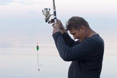 Fischer zieht Fische aus Lizenzfreies Stockfoto
