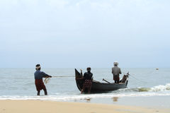 Fischer zieht sein Fischerboot Stockbilder