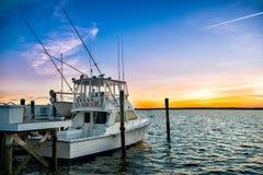 Fischerboot auf dem Pier bei Sonnenuntergang auf dem See Lizenzfreies Stockbild