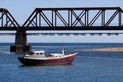Fischerboot auf dem Wasser durch die Eisenbahnbrücke Lizenzfreie Stockfotografie