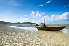 Fischerboot auf gewelltem Sandstrand Stockbilder