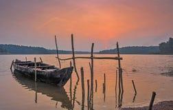 Fischerboot, das auf einem See zur Sonnenuntergangzeit stillsteht stockfotos