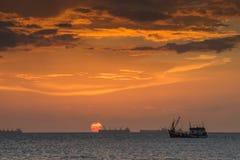 Fischerboot, das in Meer mit Sonnenunterganghimmel schwimmt Stockfoto