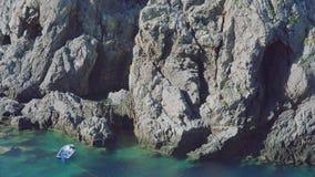 Fischerboot in der Türkis-Lagune mit enormen Felsen in Griechenland stockfotografie