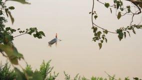 Fischerboot des Bauholzes, das entlang dem Mekong zwischen Laos und Thailand sammeln und verlassen Fischernetze treibt stock footage