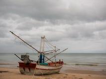 Fischerboot des Kalmars auf dem Strand am bewölkten Morgentag, mit Kokosnussbaumhintergrund Lizenzfreie Stockfotografie