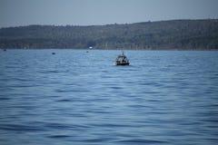 Fischerboot des weiten Schusses auf dem Wasser mit Küstenlinie im Horizont Lizenzfreie Stockfotos