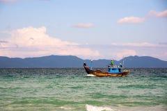 Fischerboot an einem sonnigen Tag im Ozean auf einem Hintergrund von Bergen lizenzfreie stockfotos
