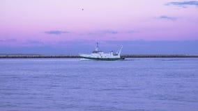 Fischerboot gibt einen Fluss bei Sonnenuntergang weiter stock footage