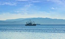 Fischerboot am grauen Morgen auf Pazifischem Ozean vor der Küste der Halbinsel Kamtschatka lizenzfreie stockfotos
