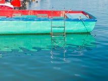 Fischerboot im Wasser mit Reflexion Stockfotografie