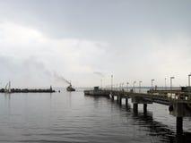 Fischerboot mit dampfendem Rohr reist vom Pier ab Stockfotografie