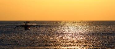 Fischerboot ohne Fischer bei Bali, Indonesien während des Sonnenuntergangs am Strand stockfotos