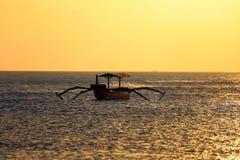 Fischerboot ohne Fischer bei Bali, Indonesien während des Sonnenuntergangs am Strand stockfotografie