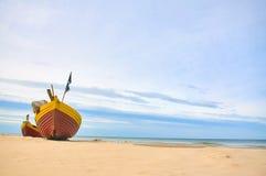 Fischerboot am sandigen Strand der Ostsee mit drastischem Himmel während der Sommerzeit Lizenzfreies Stockfoto