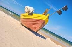 Fischerboot am sandigen Strand der Ostsee mit drastischem Himmel während der Sommerzeit Lizenzfreie Stockfotografie
