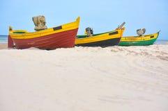 Fischerboot am sandigen Strand der Ostsee mit drastischem Himmel während der Sommerzeit Lizenzfreie Stockbilder