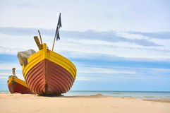 Fischerboot am sandigen Strand der Ostsee mit drastischem Himmel während der Sommerzeit Stockbilder
