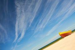 Fischerboot am sandigen Strand der Ostsee mit drastischem Himmel während der Sommerzeit Lizenzfreies Stockbild
