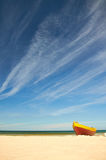 Fischerboot am sandigen Strand der Ostsee mit drastischem Himmel während der Sommerzeit Lizenzfreie Stockfotos