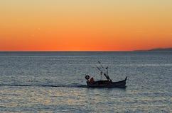 Fischerboot am Sonnenuntergang lizenzfreie stockfotos