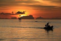 Fischerboot an Sonnenuntergang Schattenbild Stockfotos