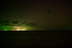 Fischerboote auf dem Ozean beleuchten den Himmel nachts Stockbild
