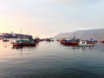 Fischerboote auf ruhigem Wasser bei Sonnenuntergang Stockfotos