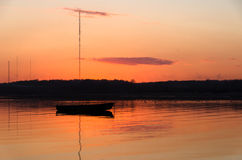 Fischerboote eins in der Bucht während eines bunten orange Sonnenuntergangs Stockfotos
