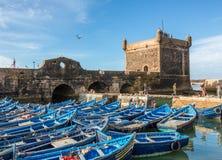 Fischerboote und Fischer mit Festung am Hafen in Essaouira, Marokko Stockfotos