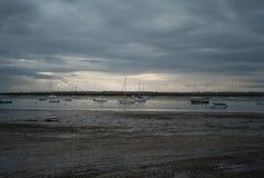 Fischerboote und kleine Boote bei Ebbe in Großbritannien am bewölkten Tag Stockfotografie