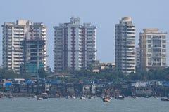 Fischerboote und Turmblöcke in Mumbai Stockfotos
