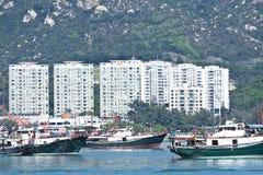 Fischerboote und Wohnblöcke in Hong Kong stockfotos