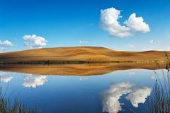 Fischerei auf einem ruhigen Wasser Hügel und Himmel lizenzfreies stockfoto