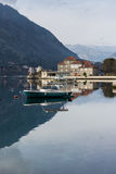 Fischerei des hölzernen Bootes mit Haus und Bergen Lizenzfreies Stockfoto