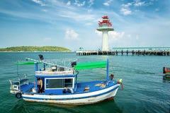 Fischerei des Schiffs im Meer und im weißen Leuchtturm Stockfoto
