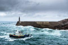 Fischerei-Fahrzeug unter dem Sturm, der im Pier ankommt Stockfoto