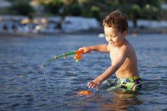 Fischereipol des kleinen Jungen und des Spielzeugs Stockfotografie